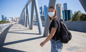 Young woman wearing a face mask walking through the streets of Melbourne, Australia on a sunny day